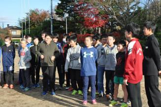 中学生の話を聞きながら陸上部の練習を見学する小学生