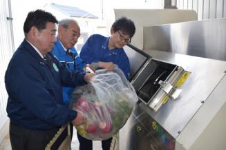 処理機に生ごみを投入する(左から)佐々木孝彦社長、小時田繁社長ら