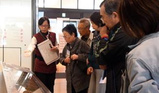 金野聡子解説員(左)の説明に聞き入る参加者