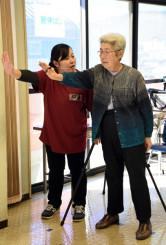 健康状態の測定方法の説明を受けるデイサービス利用者(右)