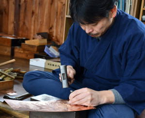 たがねで銅板に繊細な装飾を施す職人。岩谷堂箪笥の金具などを製作する=奥州市江刺愛宕・彫金工芸菊広