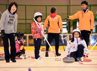 苫米地美智子さん(左)の指導を受け、カーリングを楽しむ子どもたち