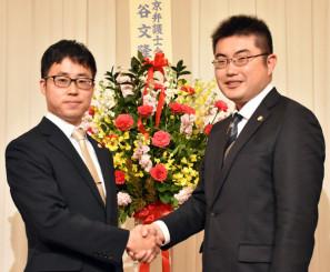 現所長の多田創一弁護士と握手を交わし、決意を新たにする細川恵喜弁護士(左)