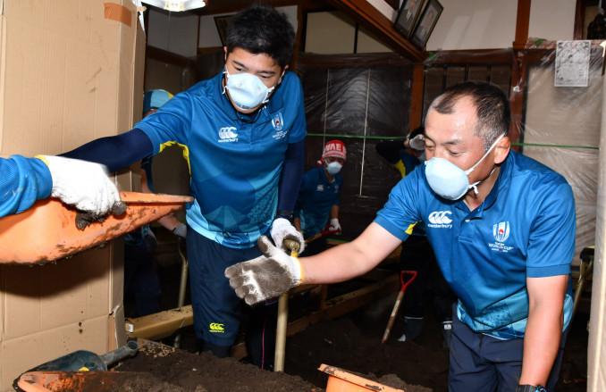 台風19号の被災地で泥出しを行うラグビーW杯2019組織委員会の有志=9日、釜石市平田