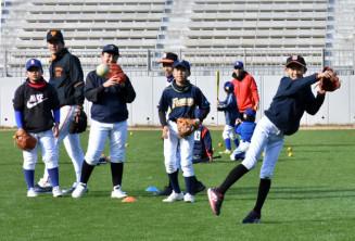 ジャイアンツアカデミーのコーチの指導でゴロの捕球や送球を学ぶ子どもたち