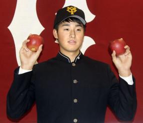 青森名産のりんごを手にポーズをとる、青森山田高の堀田賢慎投手=13日、青森市