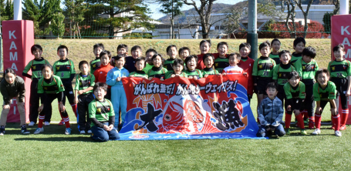 横断幕を掲げ、釜石SWにエールを送る釜石SWジュニアの子どもたち=釜石市球技場