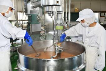 刻んだリンゴに砂糖やクエン酸を加え、ジャムを作る柏木農高の生徒たち=10月18日、青森県平川市・同校