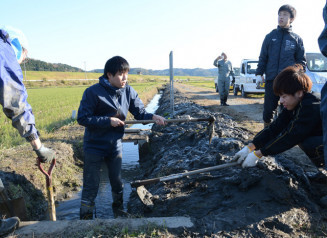 水路に入り1年分の泥をかき出す参加者