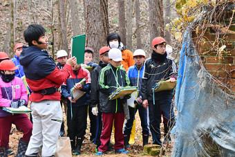 松高宏輔主事の説明を聞きながら栗木鉄山跡を見学する児童