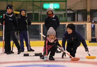 初回スクールで苫米地美智子さん(右)から基本を学ぶ子どもたち。来年3月まで開き、普及につなげる
