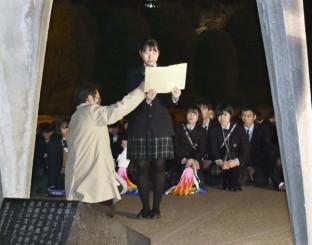 「原爆の子の像」の前で平和宣言を読み上げる中塚夏美さん=24日夜、広島市の平和記念公園