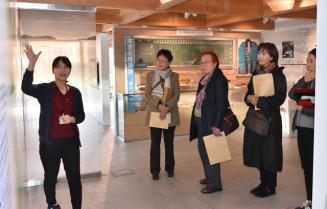 菊池のどかさん(左)から震災当時の避難所の状況などについて説明を受ける委員