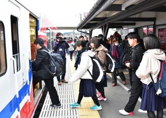 運行再開した三陸鉄道リアス線の列車に乗り込む高校生ら=28日、宮古市・津軽石駅