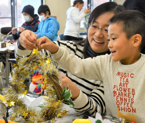 アイデアを出し合いながら、クリスマスリースの飾り付けを楽しむ親子