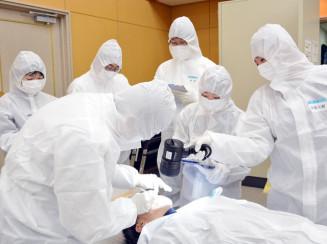 身元確認作業訓練で、歯の治療痕を確認する参加者