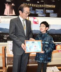 大江昌嗣理事長から記念の入館証を受ける池田崇大君(右)