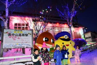 ライトアップした奥中山高原駅を背に、記念撮影する子どもたち
