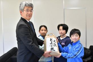 千葉浩之校長にコメを託した(右から)伊藤漣君、高木希実さん、新家真生さん