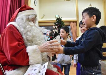 サンタクロース(左)からプレゼントを受け取る子どもたち