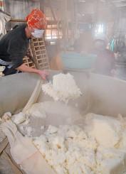 湯気が立ち上る中、蒸した酒米をスコップで運びだす小田中公さん