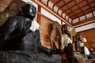 はたきを使い、丁寧に仏像のすすを払う僧侶=19日、平泉町・中尊寺