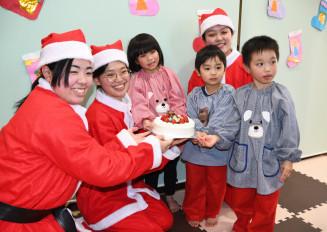 サンタ姿で、子どもたちにケーキを贈る学生たち
