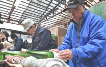 瓶詰めした日本酒に名前入りのラベルを貼る受講者たち