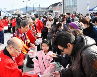 サケの大漁を祈願し来場者に餅を配る沢田克司会長(左)ら