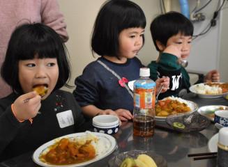 昼食のチキンカレーなどを頬張る子どもたち