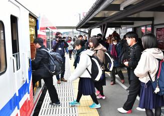 三陸鉄道リアス線の列車に乗り込む高校生ら=11月28日、宮古市・津軽石駅