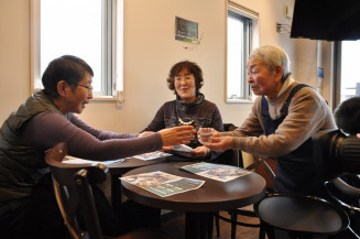 客に水を手渡すホールスタッフ(右)。認知症患者の社会参加を促し、おおらかな心を醸成した