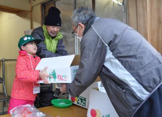 接客体験でリンゴの箱を客に手渡す児童