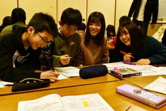 中高生ボランティアの助言を受けながら駄菓子店の名前を考える小学生