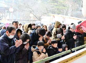 本堂前で手を合わせ、願いを込める家族連れら=1日、平泉町・中尊寺