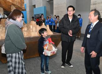 藁谷収館長(右)から入場10万人の記念品を贈られた平間大輝ちゃん(左から2人目)ら
