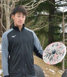 自身のイラストが描かれた花巻傘を手に、プロでの活躍を期す堀田賢慎投手=3日、花巻市内