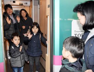 新幹線に乗り、手を振って別れを惜しむ親子連れ=4日、盛岡市・盛岡駅