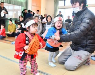 一升餅を抱え、地域住民に見守られて歩く1歳児