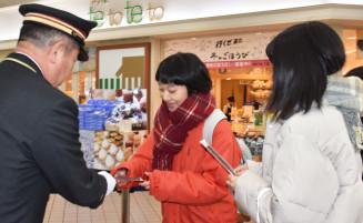 千葉利博駅長(左)から五角形の鉛筆を受け取る学生ら