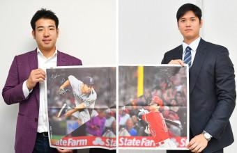 2人が初対戦した岩手日報社の記念紙面にサインを入れて掲げる菊池雄星(左)と大谷翔平