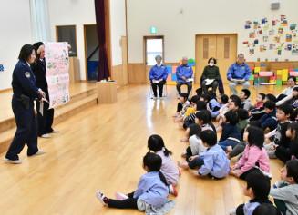 阿部真由子巡査長(左)から110番の仕組みを教わる園児