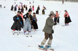 レルヒ少佐役の村里洋子会長を先頭に、はかま姿で優雅に滑る参加者たち