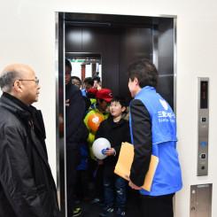 6階へ通じる真新しいエレベーターに乗り込む市民ら