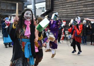 缶を打ち鳴らしながら笑顔で歌い踊る参加者