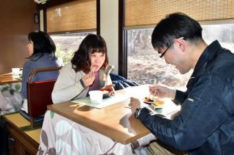 2月2日に運行開始するプレミアムこたつ列車で、海鮮弁当や瓶ドンを味わう関係者