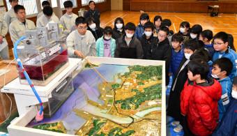 磯鶏小の児童に模型で津波の怖さを伝える宮古工高の生徒=24日、宮古市上村