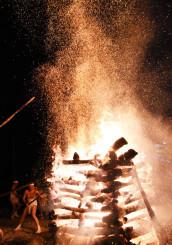 勢いよく井桁を木の棒で揺さぶり、火の粉を舞い上げる男衆=30日午後8時40分、二戸市似鳥・似鳥八幡神社