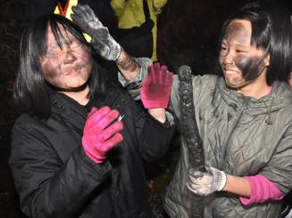 笑顔で互いの顔に炭を塗り合う参加者