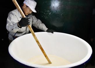 一関産こがねもちを使用した純米酒のもろみを丁寧にかき混ぜる蔵人